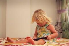 blonde Mädchenspiele mit Smartphonenahaufnahme Lizenzfreies Stockfoto