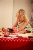 blonde Mädchenspiele mit Smartphonenahaufnahme Lizenzfreie Stockfotos