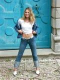 Blonde Mädchenstellung und -c$lächeln Stockfoto