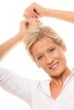 Blonde mûre de femme de portrait tenant ses longs cheveux image stock