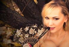 Blonde magnífico con la fan del carnaval Fotos de archivo