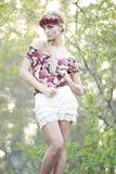 Blonde magnífico en corona roja de la flor Foto de archivo libre de regalías