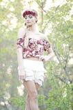 Blonde magnífico en corona roja de la flor Imagen de archivo