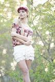 Blonde magnífico en corona roja de la flor Foto de archivo