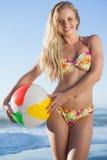 Blonde magnífico en el bikini floral que sostiene la pelota de playa Fotos de archivo