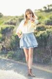 Blonde magnífico en el borde de la carretera que señala en la cámara Fotografía de archivo