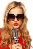 Blonde magnifique dans des lunettes de soleil avec le microphone images libres de droits