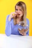 Blonde magnifique mangeant des biscuits Image stock