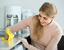 Blonde maid cleaning in domestic kitchen Royalty Free Stock Images