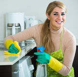 Blonde maid cleaning in domestic kitchen Royalty Free Stock Photo