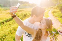 Blonde is making a selfie with her man kissing stock photography