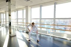 Blonde male person spotting in white suit. Blonde dancer raving in and doing spot. Young man wears white suit. Concept of rotating body and head Stock Image