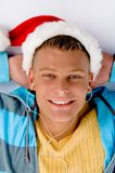 Blonde man with christmas hat and ear phones. With white background Royalty Free Stock Photo