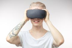 Blonde Man getting experience using VR headset glasses of virtual reality. Blonde young student man putting VR goggles on head, experiencing virtual reality Stock Photo