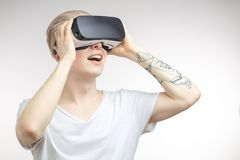 Blonde Man getting experience using VR headset glasses of virtual reality. Blonde young student man putting VR goggles on head, experiencing virtual reality Royalty Free Stock Photos