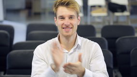 Blonde man happily claps his hands in conference hall. stock video footage