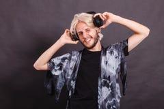Blonde man singing in studio wearing headphones Stock Photo
