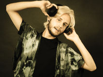Blonde man singing in studio wearing headphones Royalty Free Stock Images