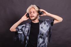 Blonde man singing in studio wearing headphones Stock Images