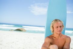 Blonde man sitting in front of his surfboard while looking towards the side Royalty Free Stock Images