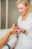Blonde Manicurist. Makes girls fingernails at beauty salon Royalty Free Stock Images