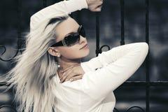 Blonde maniervrouw in zonnebril naast ijzeromheining Stock Afbeeldingen