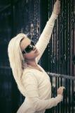 Blonde maniervrouw in zonnebril naast ijzeromheining Royalty-vrije Stock Fotografie