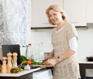 Blonde mature woman  cooking Royalty Free Stock Images