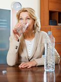 Blonde mature woman drinking water Royalty Free Stock Image