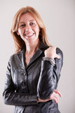 Blonde mature woman smiling in black leather Stock Photos