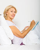 Blonde mature woman  writing in diary Royalty Free Stock Photography