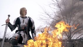 Joan of Arc in armor sits by the fire and looks around, slow motion. Blonde in medieval armor sits by the fire and holds the sword stock footage