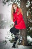 blonde meisje met rode laag in de wintersneeuw Stock Fotografie