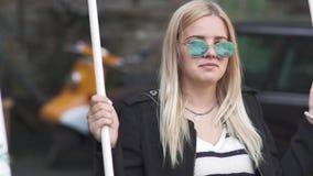Blonde meisjesschommeling bij de straat stock footage