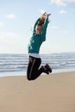 Blonde meisjessprong bij strand Stock Afbeeldingen