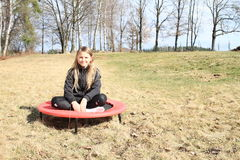 Blonde meisjeszitting op trampoline Stock Fotografie