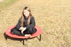 Blonde meisjeszitting op trampoline Royalty-vrije Stock Afbeeldingen