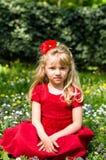 Blonde meisjeszitting in weide Royalty-vrije Stock Afbeeldingen