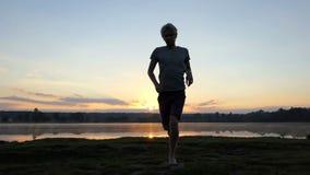 Blonde mensenlooppas van een meer aan een cameraman bij zonsondergang in slo-mo stock footage