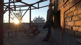 Blonde mensentribunes op een bouwwerf bij zonsondergang in slo-mo stock video