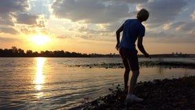 Blonde Mensentribunes op een Riverbank bij Zonsondergang hij werpt een Steen stock footage