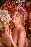 Blonde met een bloemenkroon en een creatieve samenstelling Royalty-vrije Stock Fotografie