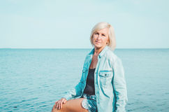 Blonde middle age woman in jeans shirt, sitting on a beach with blue sky background, copy space. Portrait of attractive Stock Photo