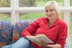 Blonde middle-aged woman is relaxing with a book in her hands Royalty Free Stock Images