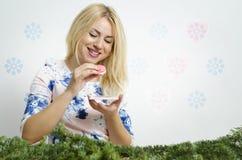 Blonde mignonne et belle mangeant le biscuit savoureux de macaron Photographie stock libre de droits