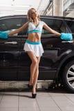 Blonde mince sexy dans le style de la formule 1 à la lave-auto images libres de droits