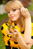 Blonde with mirror and ink for eyelashes Stock Image