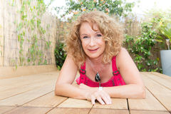Blonde mittlere Greisin, die auf Poolplattform legt Lizenzfreie Stockfotografie