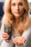 Blonde mittlere Greisin, die Pille hält Stockbild