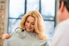 Blonde mittlere Greisin, die zuhause auf grauer modischer Kleidung versucht Lizenzfreie Stockbilder
